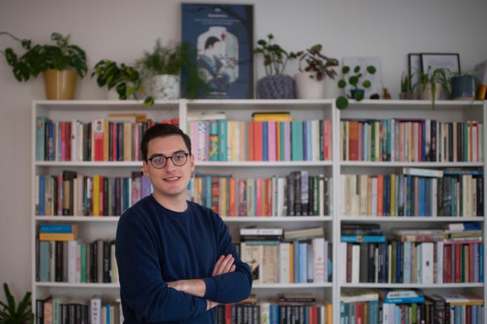Jochen De Vos voor zijn boekenkast.