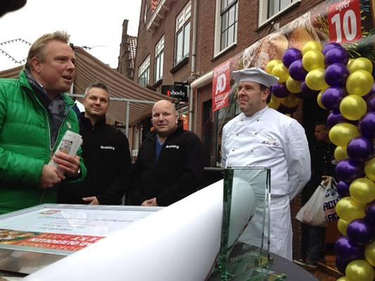 Paul van den Bosch (l) feliciteert namens de AD hoofdredactie bakkerij Brokking met de hoogste positie. Rechts: Oliebollenbakker Richard Visser die de derde plek wist te bemachtigen.