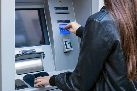 Een vrouw haalt geld af bij een bank.