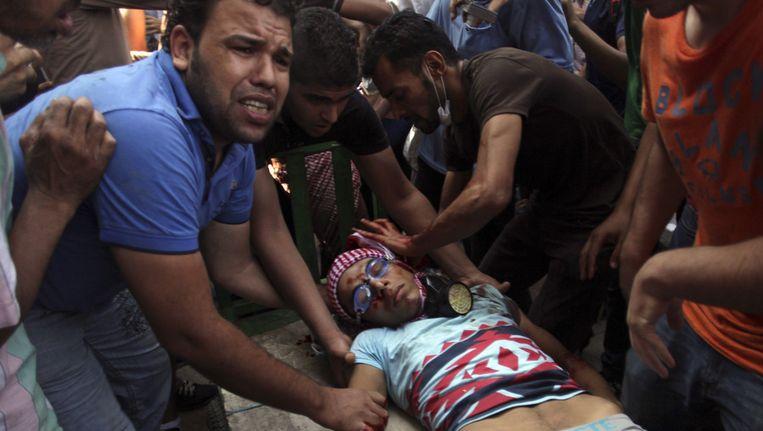 Egyptenaren voeren een man af die gewond is geraakt bij gevechten met veiligheidstroepen in het centrum van Caïro. Beeld ap