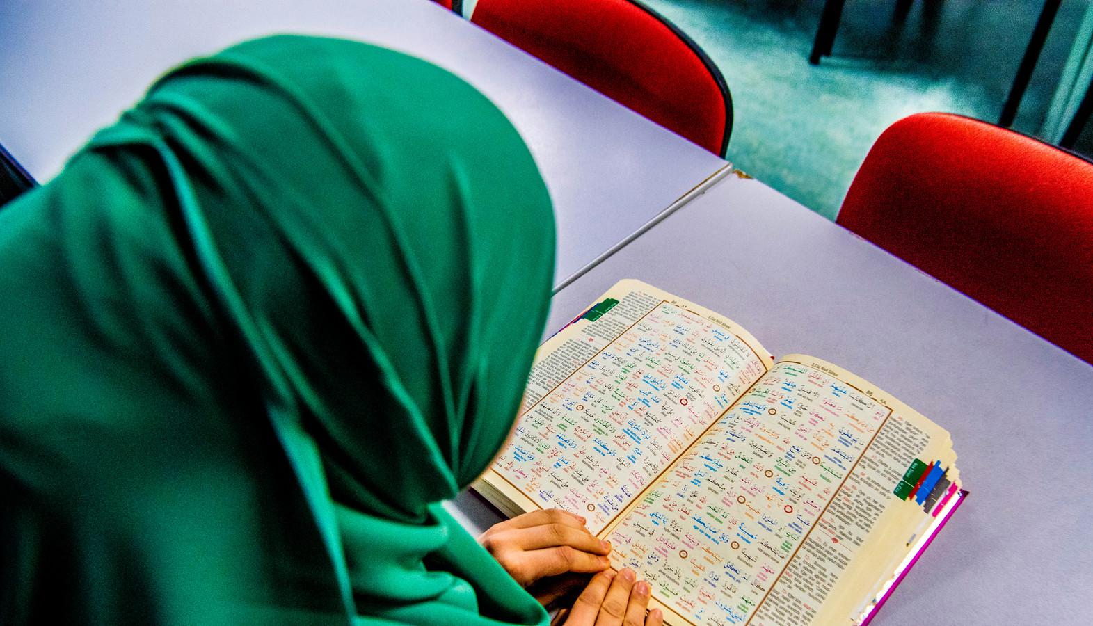 Een vrouw leest uit de koran in de moskee. Apeldoorn gaat in gesprek met de lokale moskeeën over salafistische lessen.