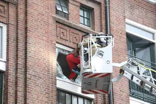 De brandweer haalt iemand uit het brandende pakhuis.