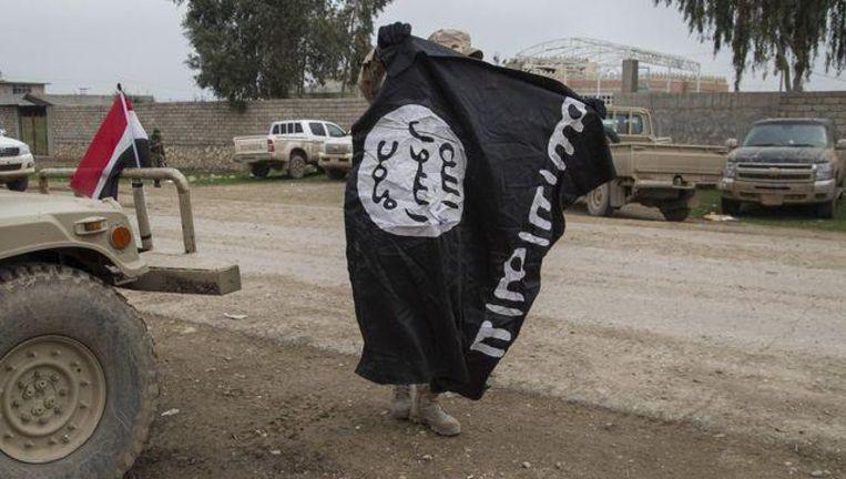 Een lid van het Iraakse leger neemt een vlag van IS in beslag in Mosoel.