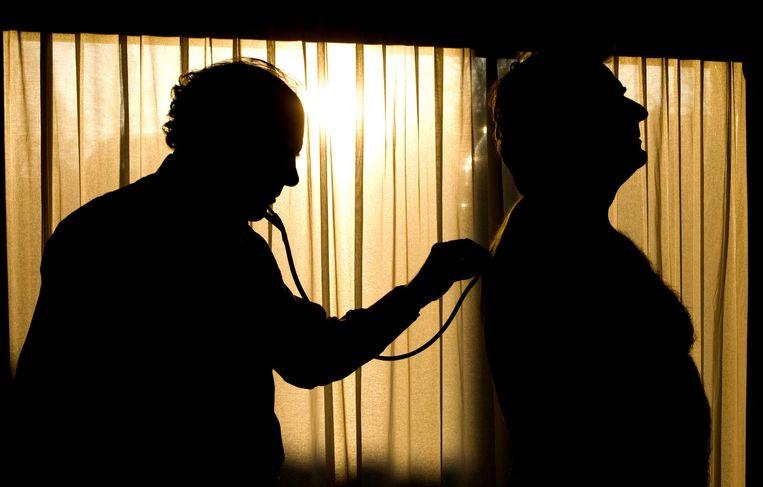 Een huisarts onderzoekt een patiënt. Beeld ANP