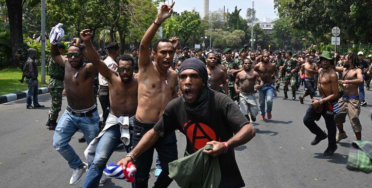 Papoeas, achtervolgd door militairen bij een demonstratie in Jakarta. Beeld AFP