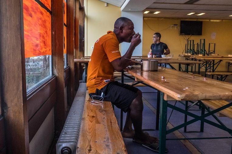 Bewoners eten in een gezamenlijke ruimte. Beeld Joris van Gennip