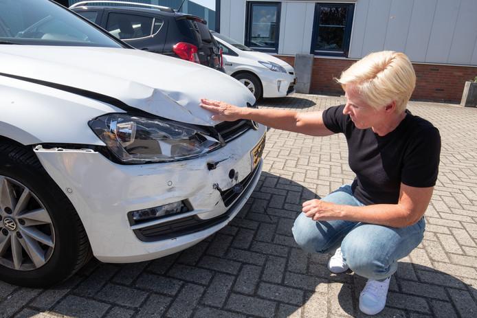 Trees de Boer bij haar beschadigde auto.