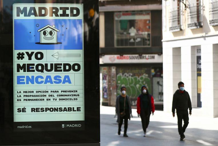 """Een poster met de tekst """"Ik blijf thuis"""" en """"wees verantwoordelijk"""" in het straatbeeld in Madrid."""