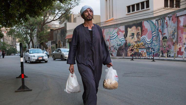 Een man loopt in Caïro langs een muurschildering waarop de armoede in Egypte wordt aangekaart. Beeld Cigdem Yuksel