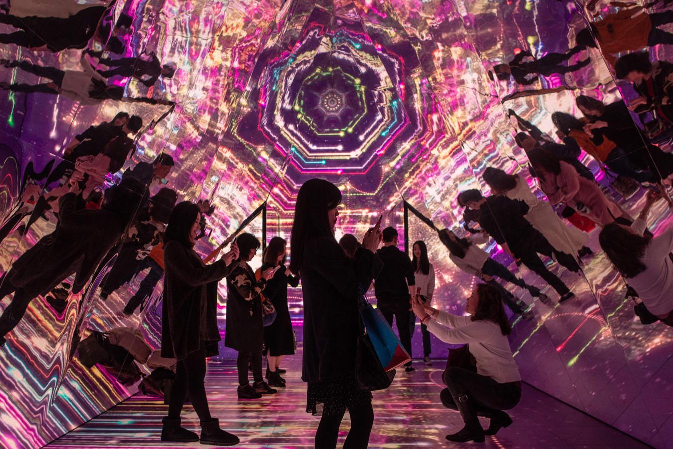 Mensen in een kaleidoscoop die deel is van kerstattracties in een winkelcentrum in Hongkong, China.