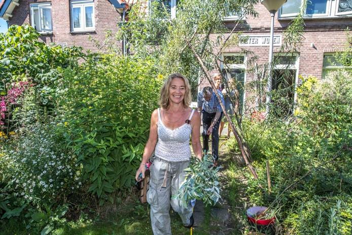 Filip van As (baant zich bukkend een weg door het groen) bezoekt Zwollenaren die al een stukje gemeentegroen adopteerden. FotoFrans Paalman