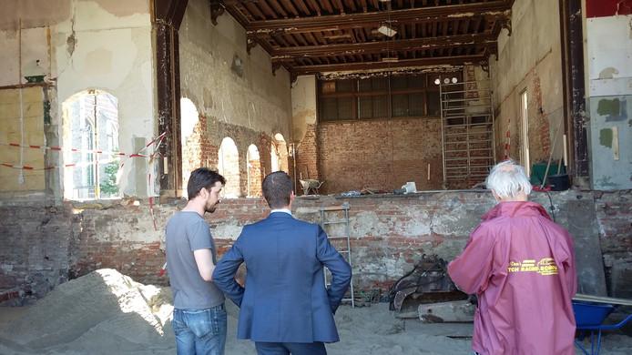 Wethouder Derk Alssema krijgt uitleg van archeologisch adviseur Karel-Jan Kerckhaert (links). Op de achtergrond de ridderzaal.