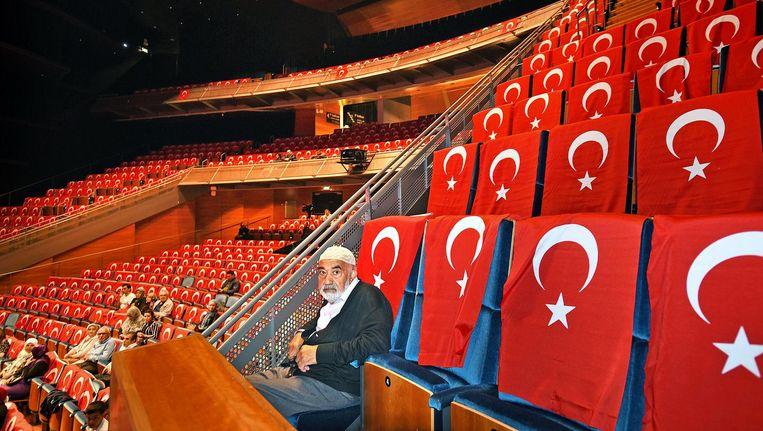 Aan het begin van de avond zit de oude man nog alleen tussen de Turkse vlaggen, maar het zou uiteindelijk niet veel drukker worden. Beeld Guus Dubbelman