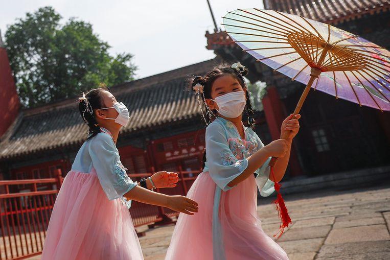 Chinese meisjes spelen met mondkapjes op in de buurt van de Verboden Stad.