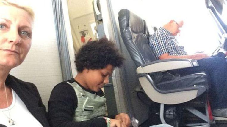 Paula Taylor met haar dochter Brooke, zittend op de vloer van het vliegtuig.