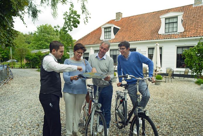 Carlos Rolsma legt de route uit die Inge Herteleer, Lieven en Laurens Bouckaert uit België willen fietsen. Het originele oude gebouw staat op de achtergrond.