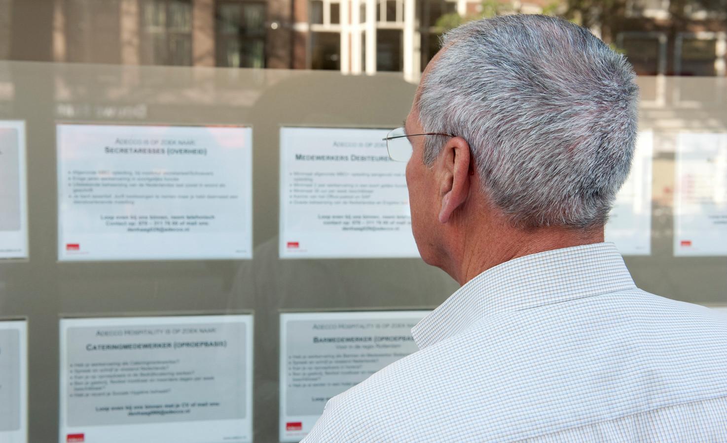 Een oudere man bekijkt vacatures bij een uitzendbureau. Meer mensen van 55 jaar en ouder hebben het afgelopen kwartaal een betaalde baan gevonden.