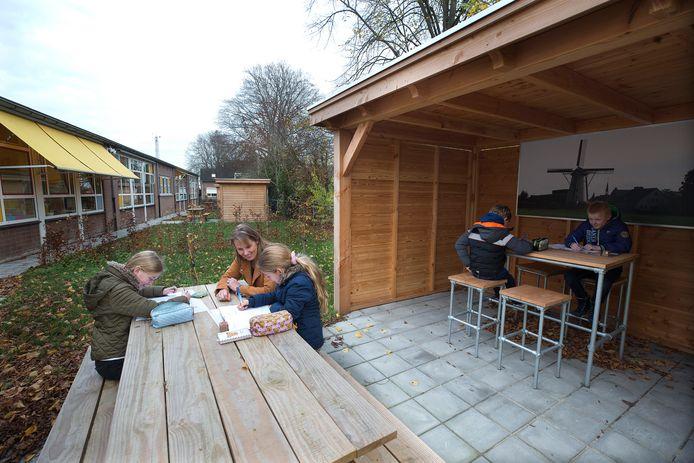 Marloes Geurtzen, directeur van de Daltonschool in Loil, aan de buitentafel met twee leerlingen.