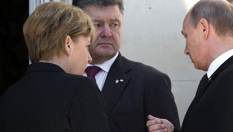 De Russische president Vladimir Poetin heeft vandaag in Normandië de tot president van Oekraïne gekozen Petro Porosjenko gesproken. Merkel was daarbij aanwezig. Beeld anp