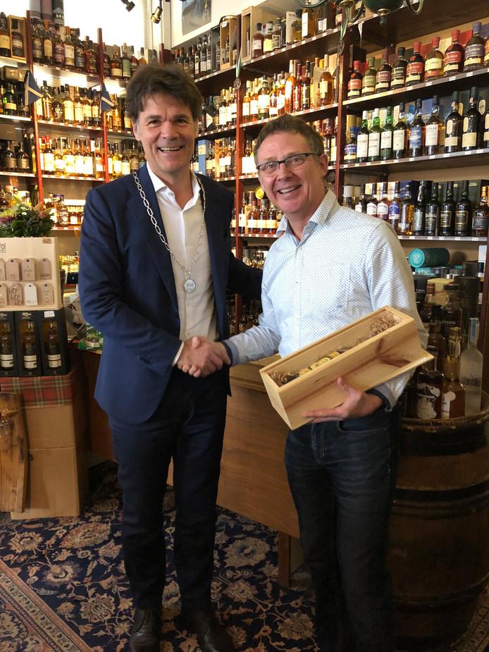 Eric Erkelens overhandigt burgemeester Depla de La Barrique whisky.