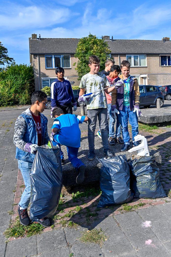 Brugklassers van het  Da Vinci College ruimen zwerfafval op in de wijk.