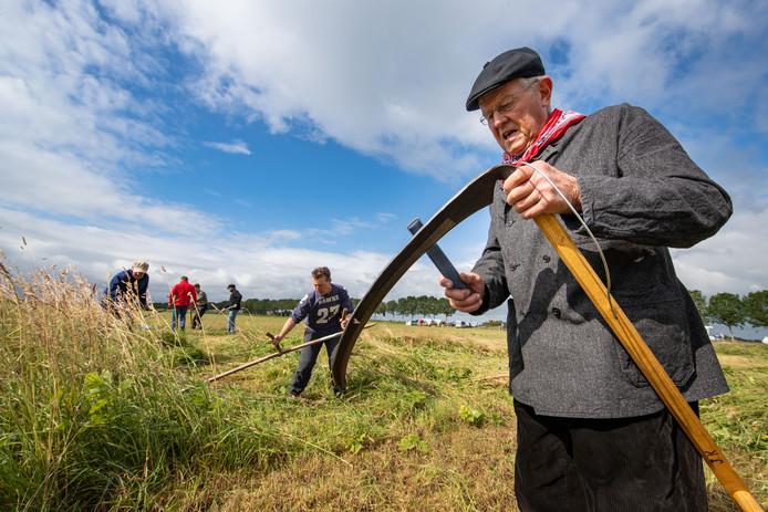 Nederlands kampioen zeis, Jan Kool uit Groningen, slijpt zijn werktuig tijdens de landelijke maaidag bij Schokland, georganiseerd door Landschapsbeheer Flevoland in samenwerking met Flevo-landschap.