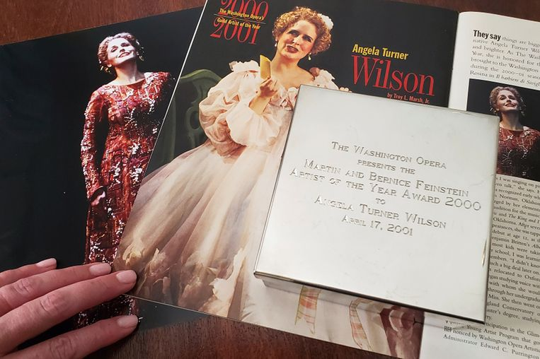 Angela TurnerWilson toont haar award voor 'Artiest van het Jaar', naast een foto van zichzelf in de opera 'El Cid'
