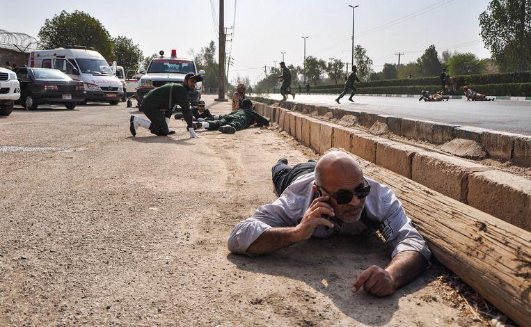 Burgers en soldaten zoeken dekking tijdens de schietpartij. Beeld AFP