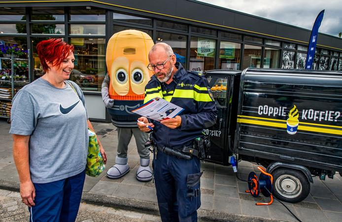 Een politieman geeft voorlichting over inbraakpreventie op het Kennedyplein in Nieuwkoop.