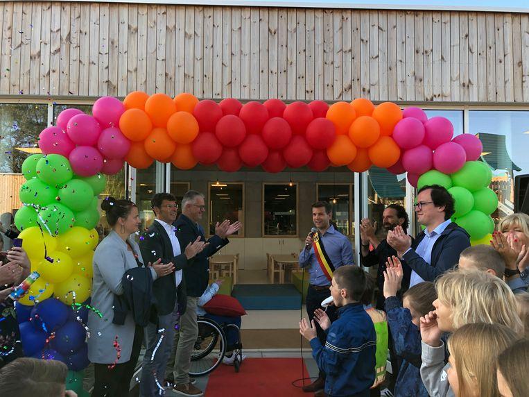 Burgemeester Jelle Wouters knipt het lint door en opent zo officieel de nieuwe kleuterschool