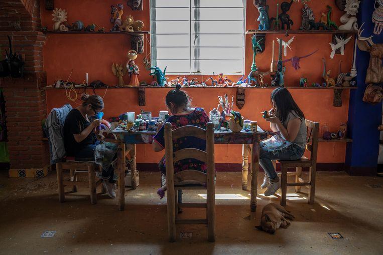 Een familie maakt houten sculpturen, 'alebrijes', in een toeristenwinkel in Oaxaca, Mexico. Beeld Alejandro Cegarra
