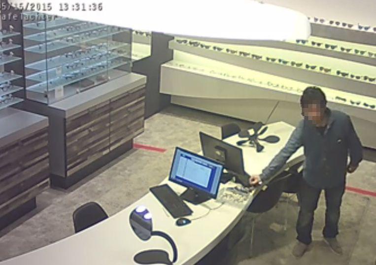 4567e5113f2ab0 Het beeld toont de dief die snel nieuwe brillen meegraait vanop de desk van het  personeel
