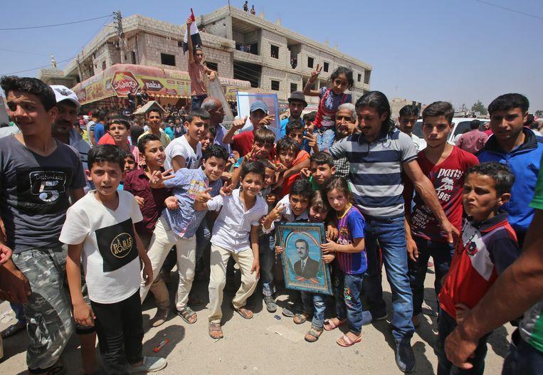 Syrische burgers poseren voor een foto kort nadat Syrische overheidstroepen het dorp Ghariyah ash Shariqiyah in de provincie Deraa hebben terugveroverd op de rebellen. Beeld AFP