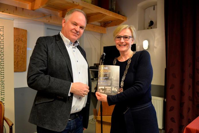 Voorzitter Frits Schultheiss van Salehem heeft het eerste exemplaar van 'Um Zellem' uitgereikt aan burgemeester Marianne Besselink van Bronckhorst.