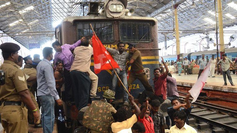 Actievoerders gaan gehurkt op de rails zitten.