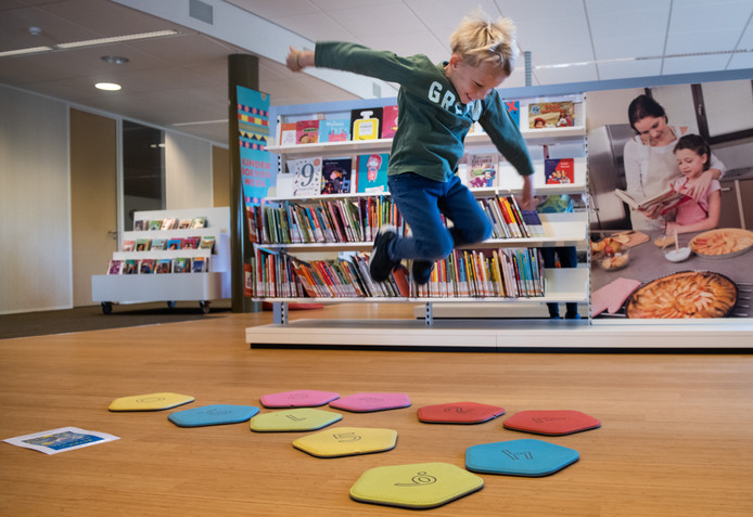 Vanwege Kinderboekenweek is in de bibliotheek in Wijchen een parcours met spelletjes uitgezet. Jort Janssen (5) springt naar het juiste cijfer als hij een som heeft opgelost.