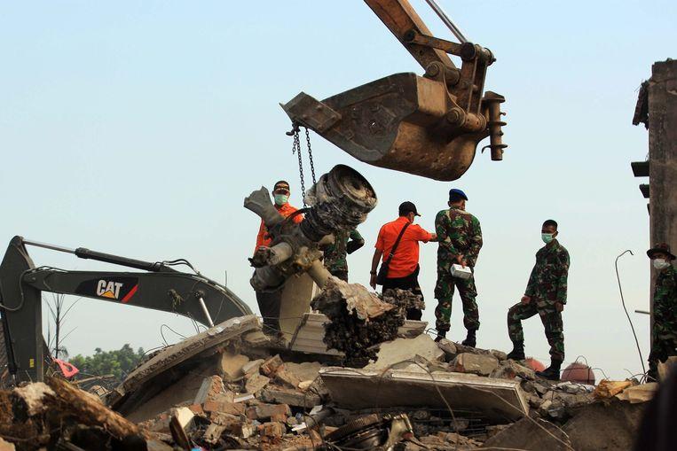 Indonesische reddingswerkers ruimen de brokstukken van het neergestorte toestel. Beeld epa