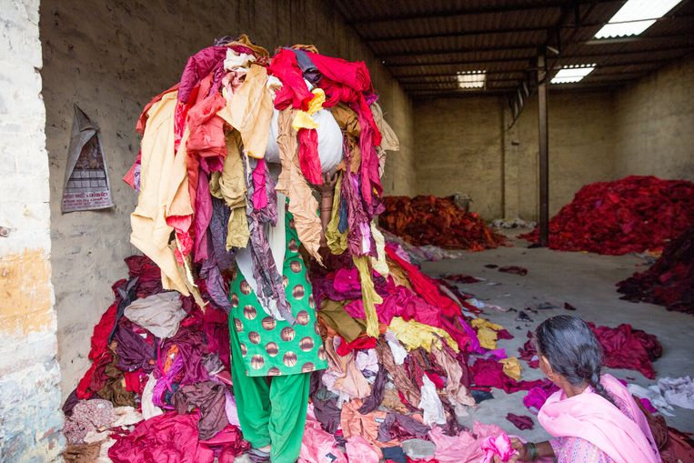 Een vrouw sorteert kleding in de Indiase stad Panipat. Ze maken er kleden en kledingstukken van. Beeld RUHANI KAUR