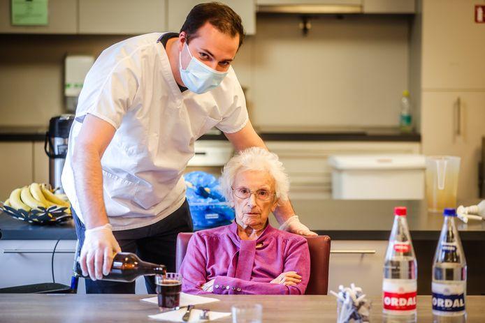 Nick Blontrock schenkt een glaasje in voor een bewoonster van woonzorgcentrum Zeventorentjes in Assebroek.