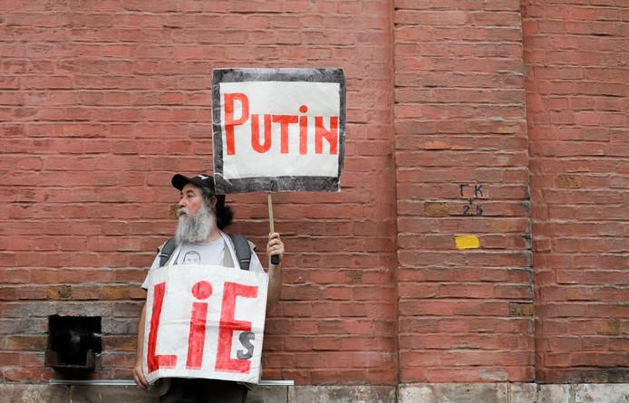 Een demonstrant houdt borden op met de boodschap 'Poetin liegt'.