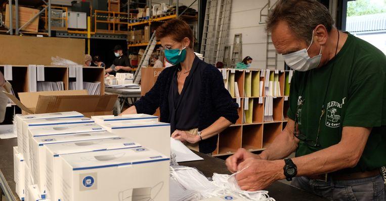 Vrijwilligers verpakken en verdelen de mondmaskers