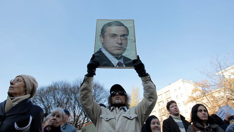 Een demonstrant houdt een portret van de Russische zakenmagnaat Michael Chodorkovski vast. Beeld REUTERS