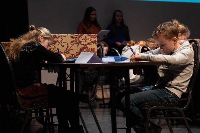 Twee deelnemers aan het Junior Dictee Rijssen concentreren zich op lastige spellingopgaven.