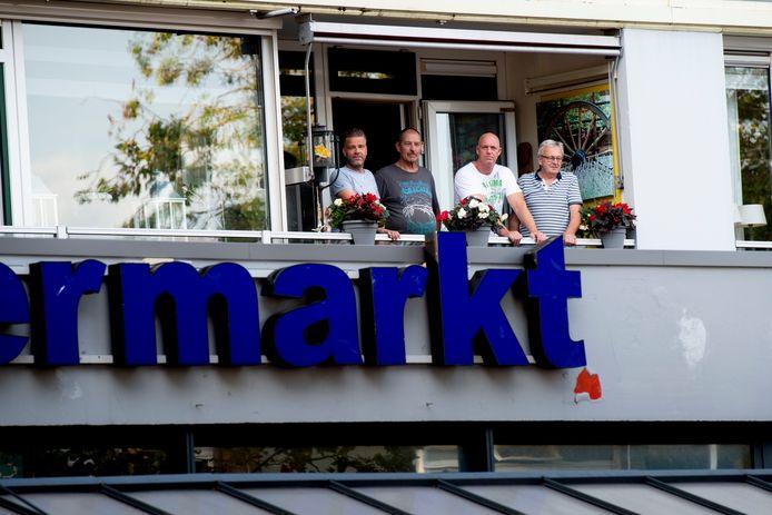Erwin Huisman (tweede van rechts) op het balkon van de woning die hij aan de ondergelegen supermarkt heeft verkocht.
