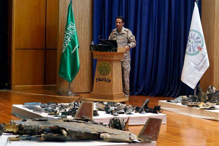 De legerwoordvoerder van Saoedi-Arabië, kolonel Turki Al-Malik tijdens de persconferentie tussen brokstukken van drones en kruisraketten die gebruikt zijn bij de aanval dit weekend op olie-installaties in het land.  Beeld EPA / STRINGER