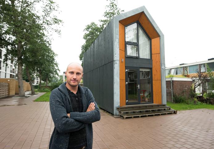 Freek van Capelle bij de tiny house op de groenstrook achter de flats aan de Rooseveltlaan in Kaneleneiland.