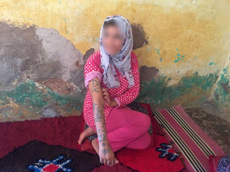 Khadija Okkarou doet haar verhaal aan de media. Onder de tatoeages die haar toegebracht werden, is ook een hakenkruis. Beeld AFP