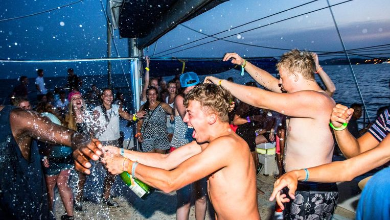Feestende Nederlandse jongeren tijdens een zogenaamde Sunset Party Cruise voor de kust bij de Spaanse badplaats Blanes. De jonge vakantiegangers kunnen bij deze excursie genieten van de zonsondergang terwijl ze drinken en dansen op een boot. Beeld anp