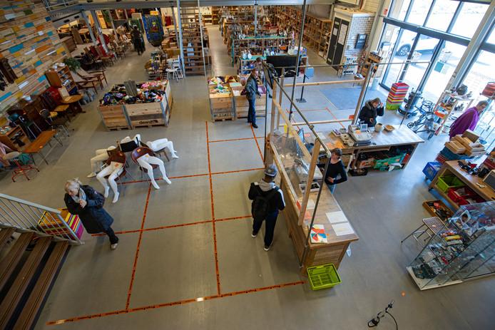 In de kringloopwinkel aan de Ambachtsstraat in Kampen zijn met tape vakken op de grond aangegeven zodat mensen voldoende afstand tot elkaar kunnen houden.