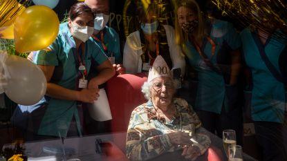 Taart en champagne! Irena viert 100ste verjaardag met familie achter het raam